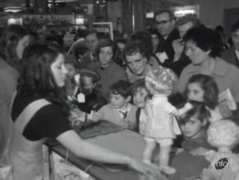 Image taken from an ITN news report showing a shop assistant demonstrating toys to shoppers in 1970