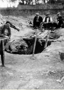 Image of a coal hole during the 1926 miner's strike, showing four miners sitting around the hole and one miner in the hole. From the 'Picture the Past' Collection.