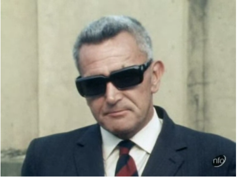 Still from an interview with a professional shoplifter, who is wearing a suit and sunglasses. Taken from the News at Ten, 1970.