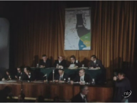 Still of a news report on the auction of North Sea oil sites, which took place in 1971. The image shows the auction delegation sitting in front of a map of the North Sea.