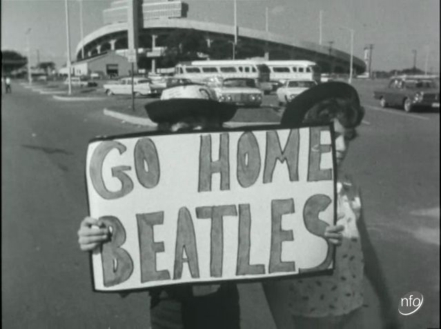 """still image showing to young women holding up a hommade placard saying """"Go Home Beatles""""."""