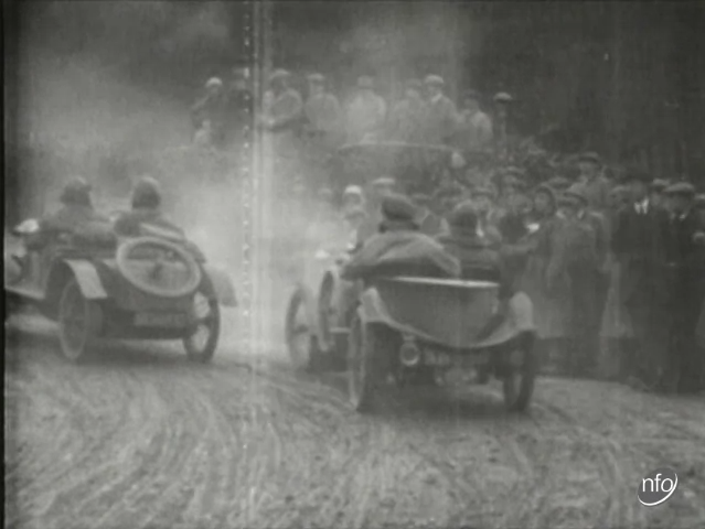 Still of a news report showing cars taking part in the motorcyle and car trail run between London and Exeter which took place in 1919.