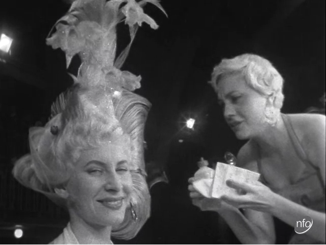 Still image taken from a news report, showing a woman putting glitter on a model's hair.