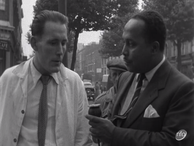Image of a man interviewing a shop owner following race riots in Notting Hill in 1958.