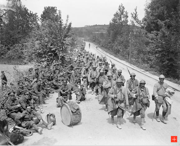 An image showing French infantry marching through Passy-sur-Marne and passing British infantry resting by the roadside. Taken on 29 May 1918 during the Battle of the Aisne.