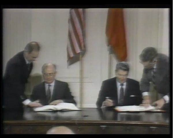 Screenshot of Mikhail Gorbachev and Ronald Reagan sitting side by side signing declarartions. 1990.