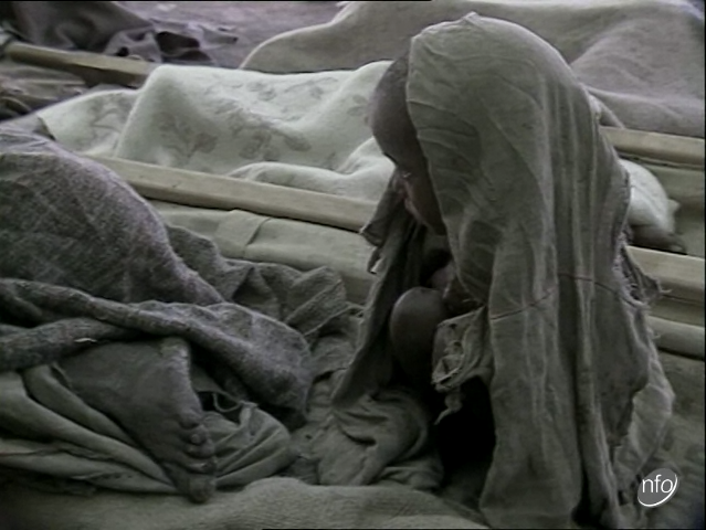 Film still showing a young child wrapped in a cloth shivering in the cold in an Ethiopian relief camp