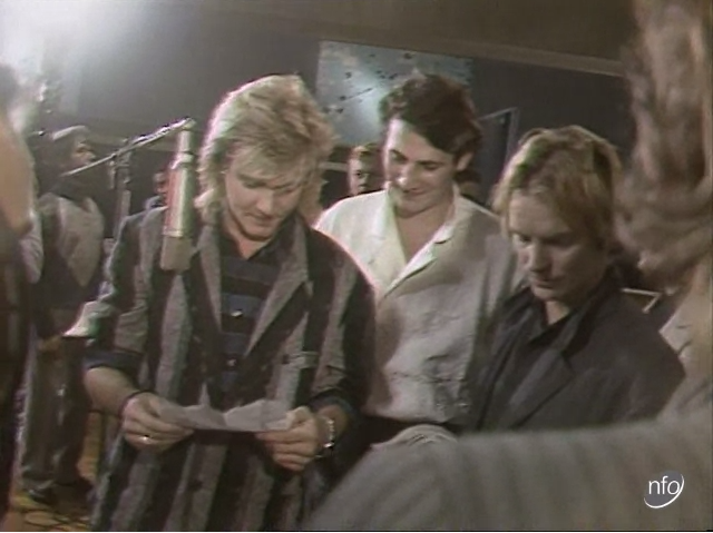 """Film still of Simon Le Bon, Tony Hadley and Sting around a mike singing """"Do They Know It's Christmas?"""""""