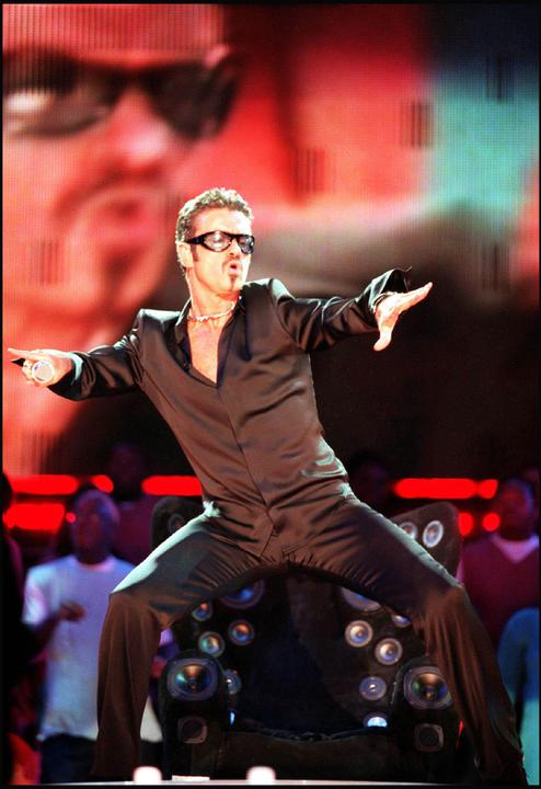 A photopgraph of George Michael performing on stage at NetAID.