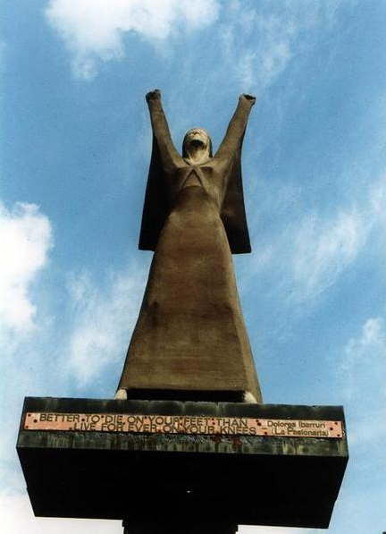 Photoograph of the sculpture called 'La Pasionaria', a stylised female figure, representing Dolores Ibarruri, in a long dress, standing with legs apart and arms raised.