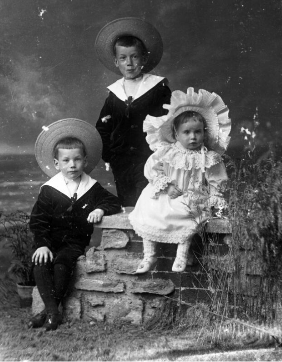 A photograph of three children - one girl in white suit and hat, and her two brothers in black sailor suits with white collars, taken circa 1905.