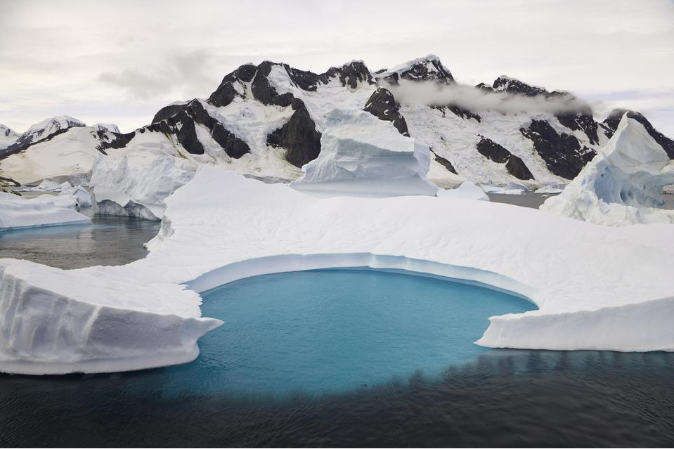 A photograph of icebergs stranded in a shallow bay and an emerald pool of water in the Antarctic Peninsula.