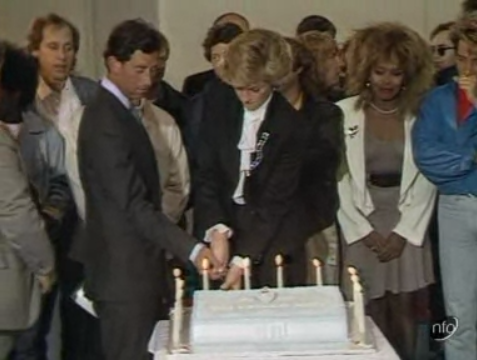 Still from a news report showing the Prince and Princess of Wales, surrounded by British rock stars, cutting a cake celebrating the 10th anniversary of the Prince's Trust.