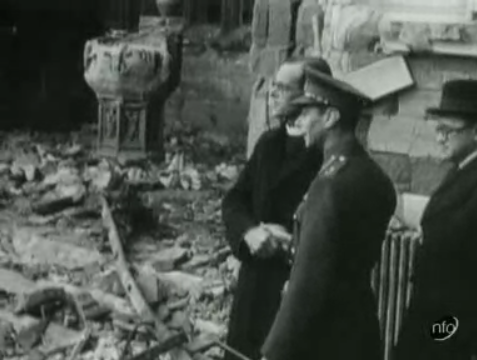 A screenshot from a news report on HM the King inspecting German bombing raid damage on Coventry Cathedral in 1940.