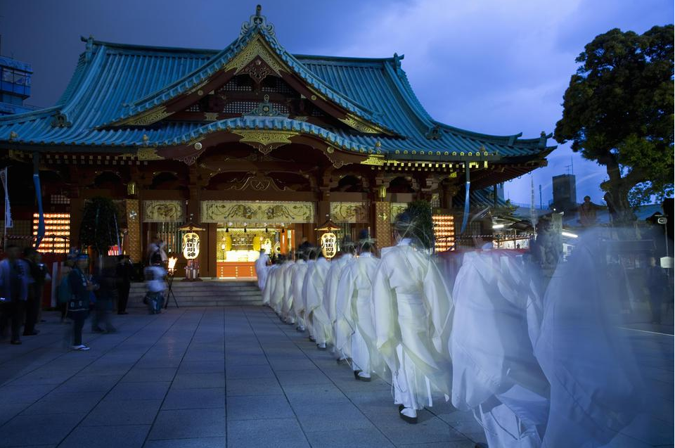 An image showing a procession of Shinto Priests wearing the white costume of Kanda-Matsuri, walking towards a Shinto temple.