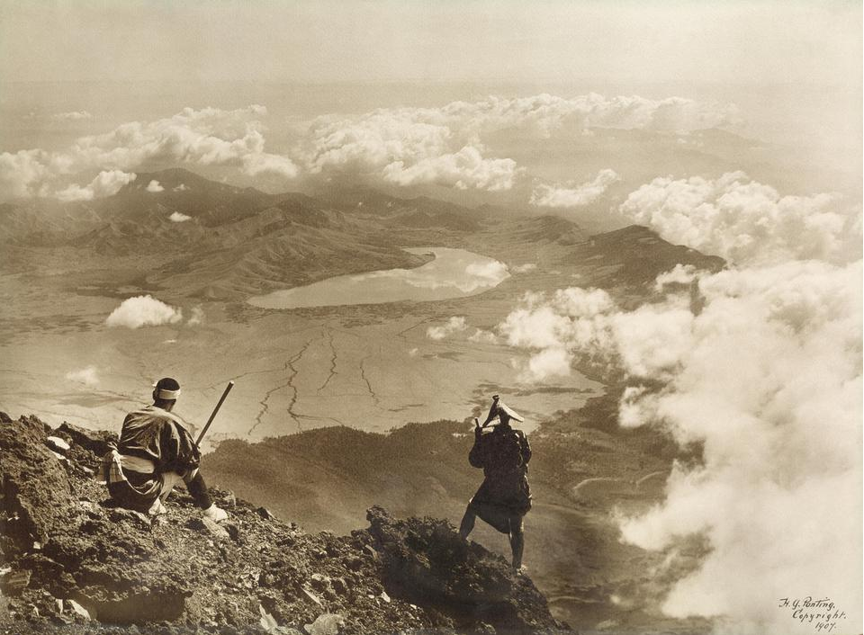 A landscape photograph of Lake Yamanaka from the Summit of Mt Fuji, showing mountains and lake with two people in foreground.