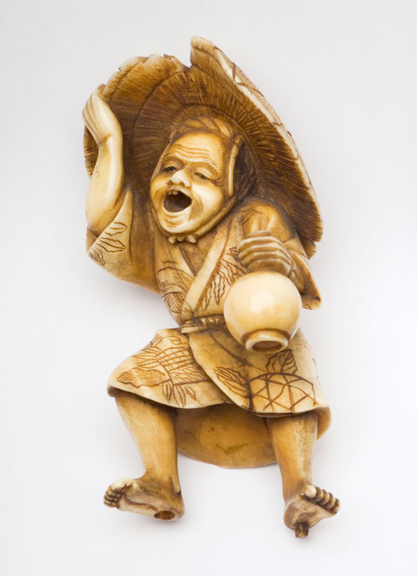 An image of a stained ivory okimono of a barefoot artisan holding a bottle vase from the Meiji period.